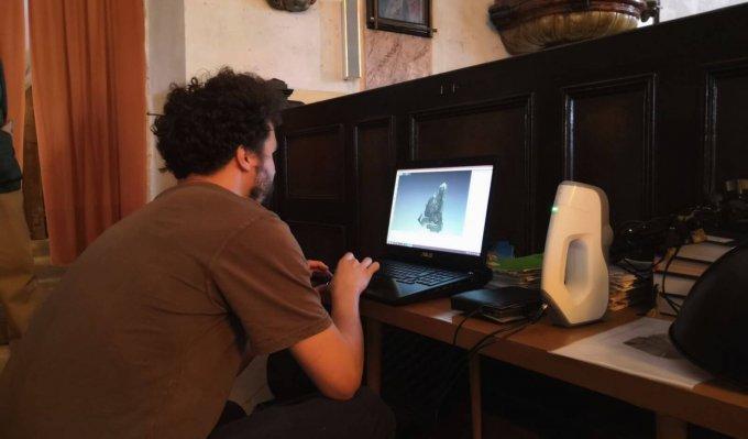 Operátor v notebooku prohlíží data získaná v průběhu skenování náhrobku