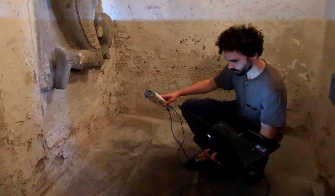 Operátor snímá skenerem historický náhrobek umístěný na zdi
