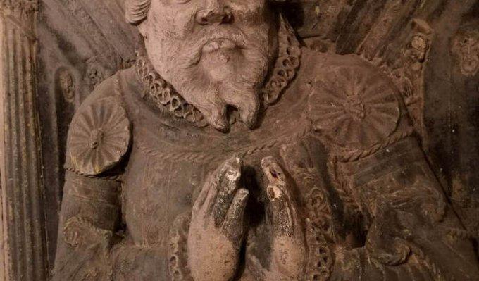 Historický kamenný náhrobek na přední straně je reliéf modlící se postavy pochovaného muže