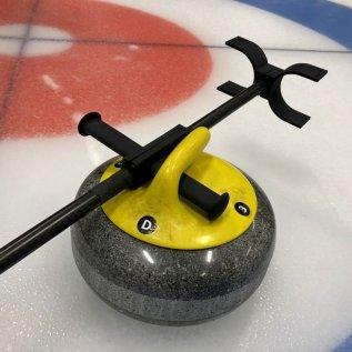 3D tištěná hůl pro curling položená na curlingovém kameni