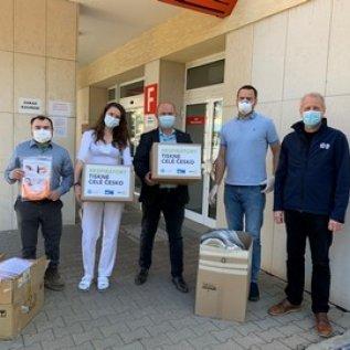 Zástupci výrobce předávají pracovníků zdravotnického zařízení krabice s 3D vytištěnými respirátory