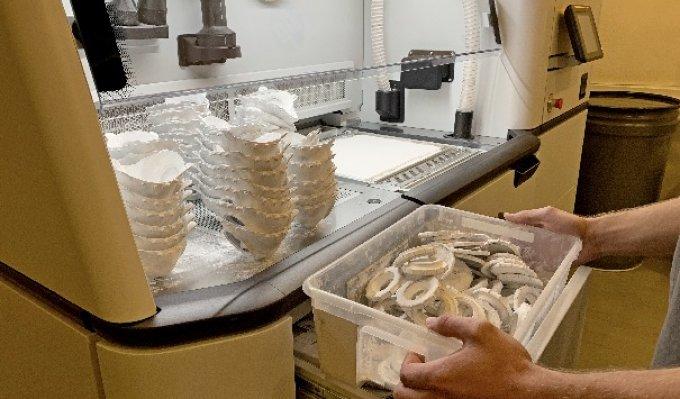 Operátor 3D tiskárny z ní vyndává vytištěné respirátory