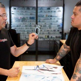 Dva designéři stojí u stolu a prohlíží si barevné obroučky brýlí Oakley vyrobené 3D tiskem