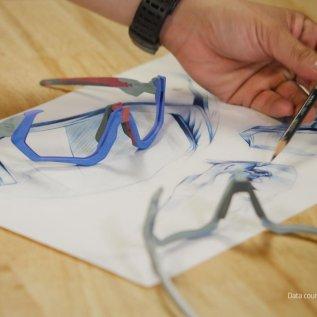 Barevné obroučky brýlí Oakley z 3D tiskárny leží na stole vedle technického výkresu