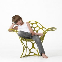 Dítě školního věku sedí na židli organického tvaru vyrobené pomocí 3D tisku