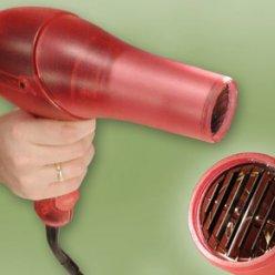 Prototyp fénu v červeném a mírně průhledném provedení a držený v ruce