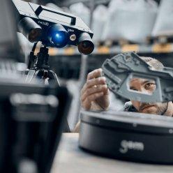 Operátor umisťuje skenovaný díl na rotační stůl a v pozadí je na stativu 3D skener GOM ATOS Q