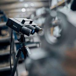 3D skener GOM Atos Q na stativu v detailním záběru ve výrobní hale