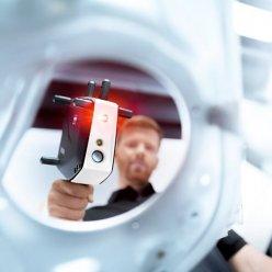 Průhled kulatým otvorem ukazuje 3D skener ZEISS T-SCAN  v rukách operátora se zapnutým laserem
