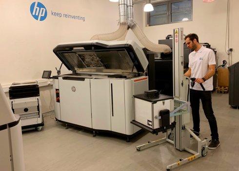 An operator works on an HP 5200 3D printer