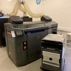 3D tiskárna stojí v místnosti a je napojená na odtah vzduchu, před ní je volně stojící mobilní build unit