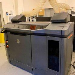 3D tiskárna stojí v místnosti a je napojená na odtah vzduchu