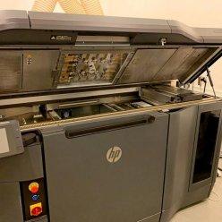3D tiskárna s otevřeným horním krytem stojí v místnosti