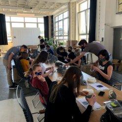 U dlouhé řady stolů sedí tým operátorů, kteří kompletují respirátory na jednotlivých pracovištích