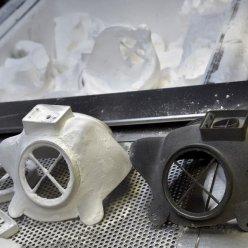 Na kovové podložce jsou dva hlavní díly 3D vytištěného respirátoru v bílé a černé barvě