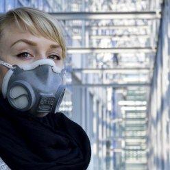 Modelka s nasazeným respirátorem vyrobeným 3D tiskem pózuje v prosklené budově