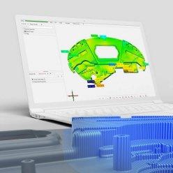 Na displeji notebooku je vizualizovaný díl, který je v popředí snímám skenerem pomocí projekce modrého světla
