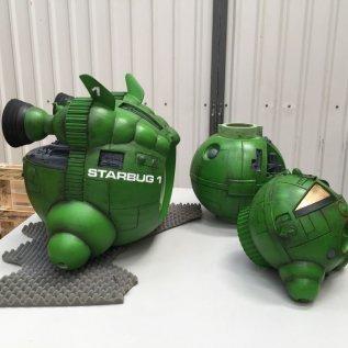 Díly vesmírné lodi z 3D tiskárny Voxeljet položené na bílém stole, nabarvené do syté zelené barvy