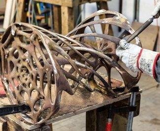 Organický tvar odlitého kovového dílu opracovávaný dělníkem