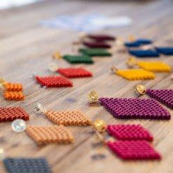 Náušnice různých velikostí a barev kosočtvercového tvaru s korálkovou strukturou na stole