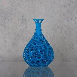 Modrá váza organického tvaru na lesklém stole před šedým pozadím