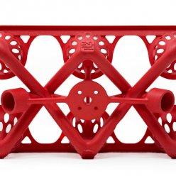 Červený díl se složitou strukturou na bílém pozadí