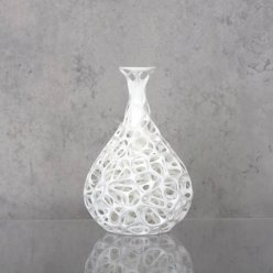 Bílá váza s organickou strukturou na lesklém stole před šedým pozadím