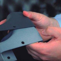 Plastový díl v původní šedé barvě z výroby a obarvený do finální černé v rukou operátora