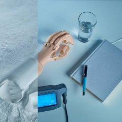 Protetická ruka vyrobená v surovém stavu v 3D tiskárně a ve finální podobě položená na psacím stole