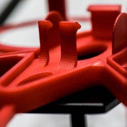 Červený díl vyrobený 3D tiskem se spojovacími západkami.