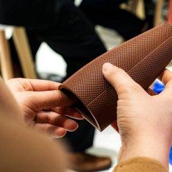 Hnědý umělecký předmět kónického tvaru v rukou zájemce