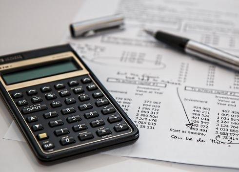 Na vytištěných finančních výkazech je položená kalkulačka