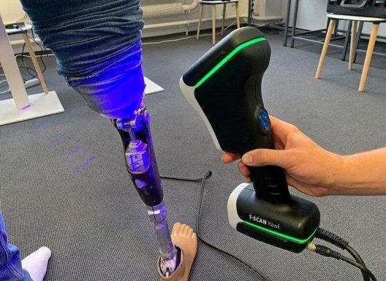 3D skener v ruce operátora snímá protézu pravé nohy stojící osoby