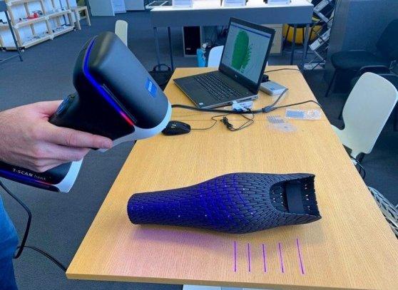 3D skener v ruce operátora snímá 3D výtisk krytu protézy nohy ve tvaru lýtka