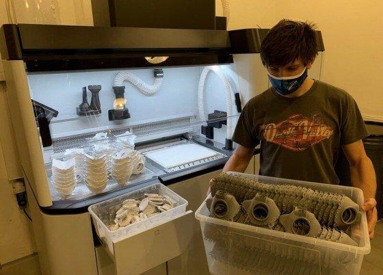 Operátor přenáší vytištěné polomasky od 3D tiskárny