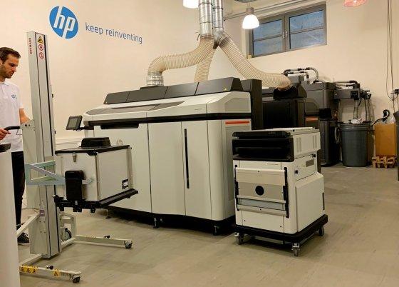 Operátor přiváží natural cooling jednotku k build unit vyjmuté z průmyslové tiskárny HP